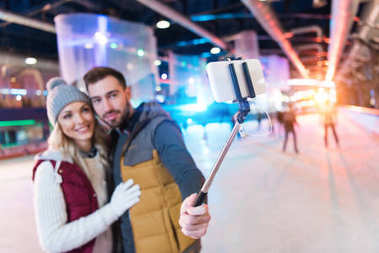 selective focus of happy young couple taking selfie with smartphone on rink