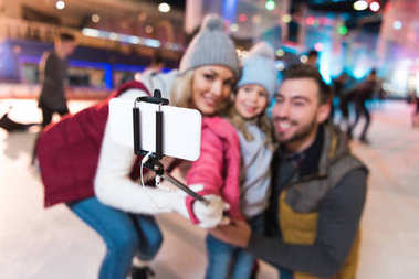 selective focus of happy young family taking selfie with smartphone on skating rink