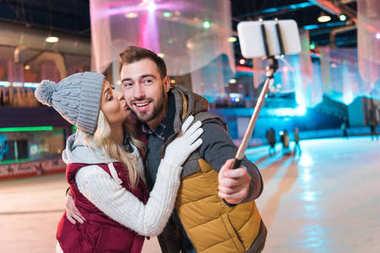 happy young couple taking selfie with smartphone on rink