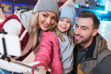 happy young family taking selfie with smartphone on skating rink