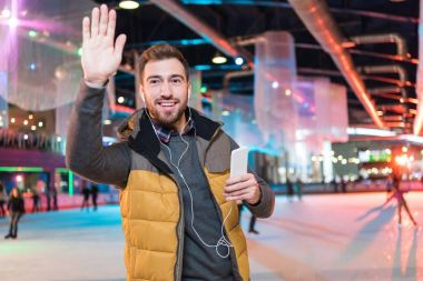 smiling young man in earphones holding smartphone and waving hand while standing on rink
