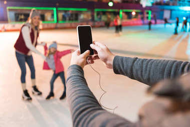 cropped shot of man holding smartphone with blank screen and photographing family skating on rink