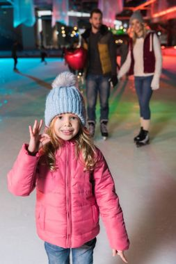 Cute little girl showing ok sign and smiling at camera while ice skating with parents on rink stock vector