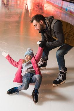 father holding hand of cute little daughter falling on rink