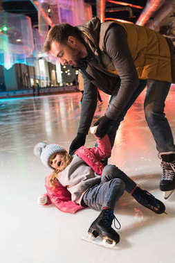 father helping little daughter lying on ice on rink