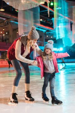 beautiful happy mother and daughter ice skating together on rink