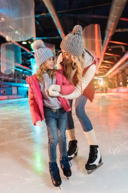 Happy mother and daughter holding hands and smiling each other on skating rink stock vector