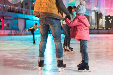 Cropped shot of father and daughter holding hands while standing together on skating rink stock vector