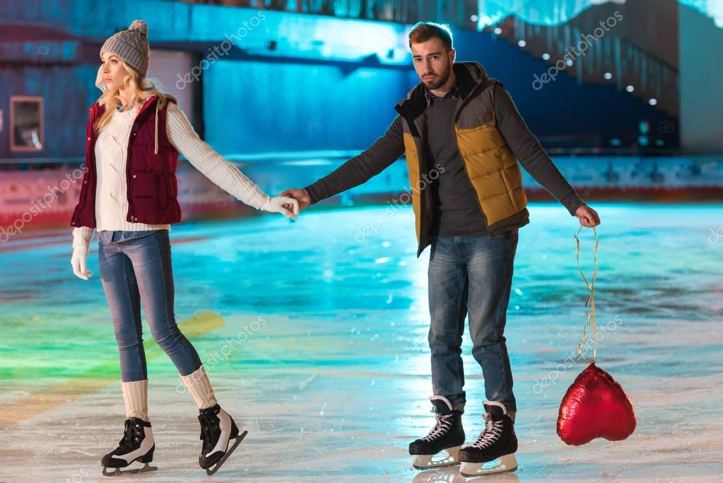 young couple holding hands while man holding heart shaped balloon on rink