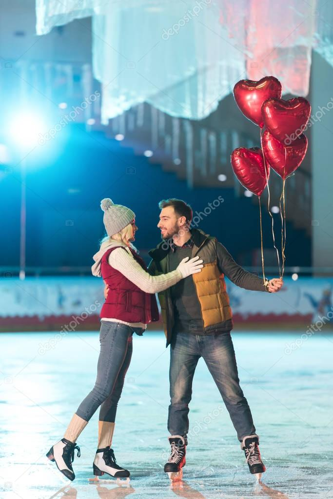 beautiful happy young couple with heart shaped balloons smiling each other on rink