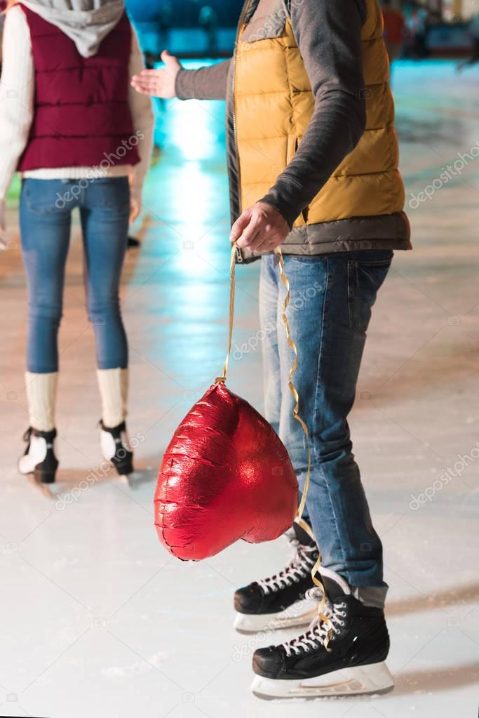 partial view of young man holding heart shaped balloon while girlfriend going away on rink