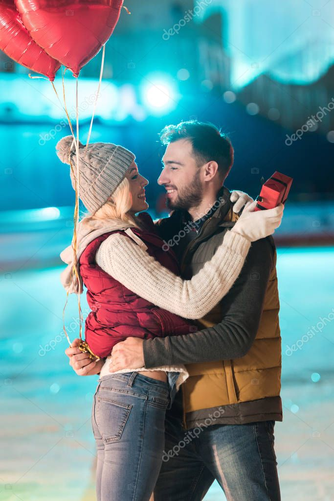 Happy young couple with gift box and heart shaped balloons looking at each other on skating rink stock vector