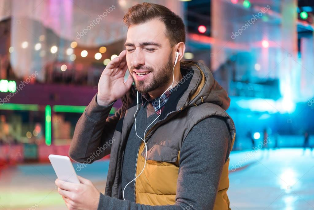 happy young man with closed eyes listening music with smartphone while ice skating on rink