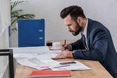 Geschäftsmann am Tisch sitzen, mit Blick auf Dokumente und etwas zu schreiben