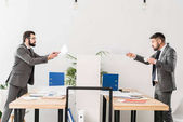 businessmen quarreling in office and showing documents each other