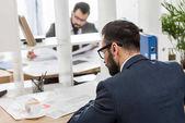 üzletemberek polcok között működő asztaloknál ül