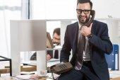 Fotografie podnikatel mluví o stacionární telefon v kanceláři a sedí na stole
