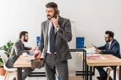 usmívající se podnikatel mluví stacionární telefonicky v kanceláři