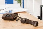 sluchátko černý stacionární telefon na stole