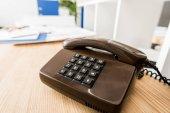 černý stacionární telefon na dřevěný stůl