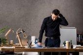 promyšlené architekt stojící vedle pracovního stolu a při pohledu na plány