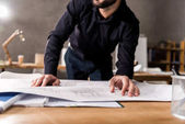 cropped image of architect looking at blueprints on table
