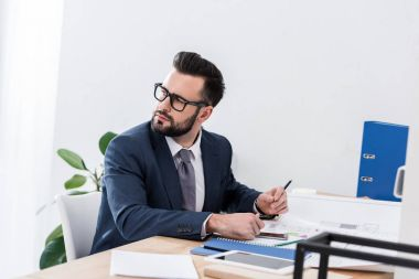thoughtful businessman sitting at working table and looking away