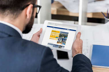 businessman holding tablet with loaded booking page