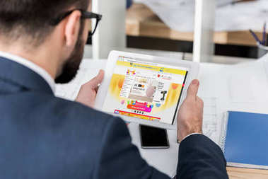 businessman holding tablet with loaded aliexpress page