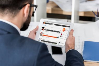 businessman holding tablet with loaded soundcloud page