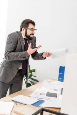 irritated businessman holding documents and screaming at someone
