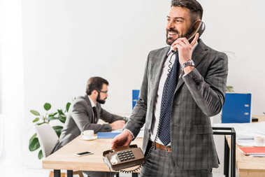 smiling businessman talking by stationary telephone in office