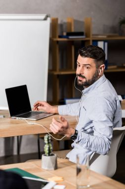 handsome businessman sitting at laptop and asking colleague for something