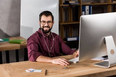 smiling businessman working at computer in office and looking at camera