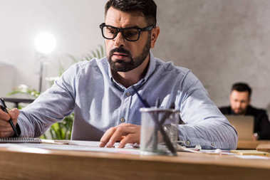 handsome businessman writing something to notebook at working table