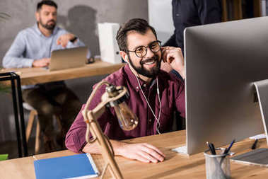 smiling businessman working at computer in office and listening music with earphones