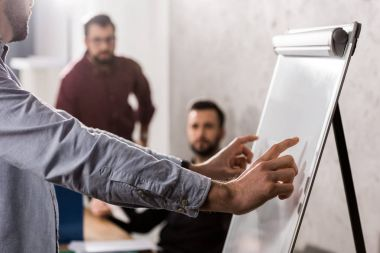businessman pointing on something at flipchart in office