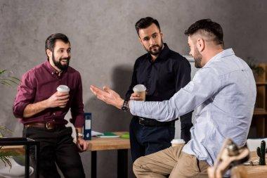 smiling handsome businessmen talking during coffee break at office