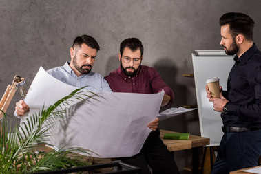 architects looking at blueprints at working space