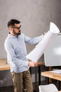 handsome architect looking at blueprint in office