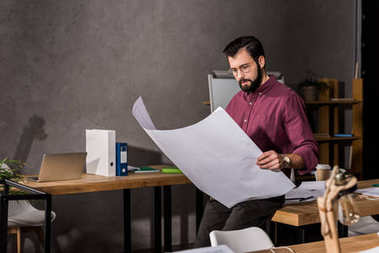 Thoughtful handsome architect looking at blueprint in office stock vector