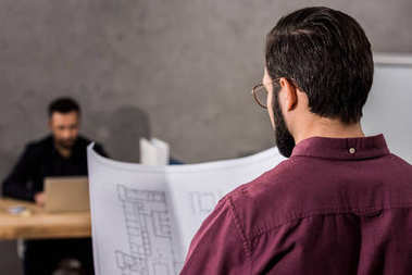 rear view of architect looking at blueprint in office