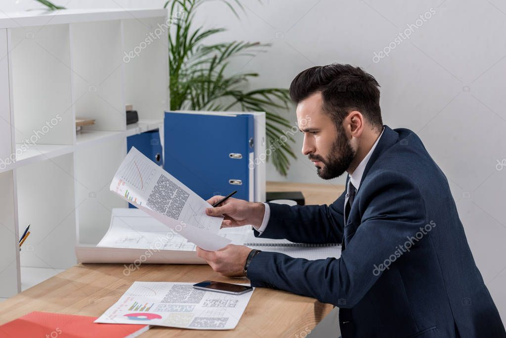 businessman sitting at working table and looking at documents