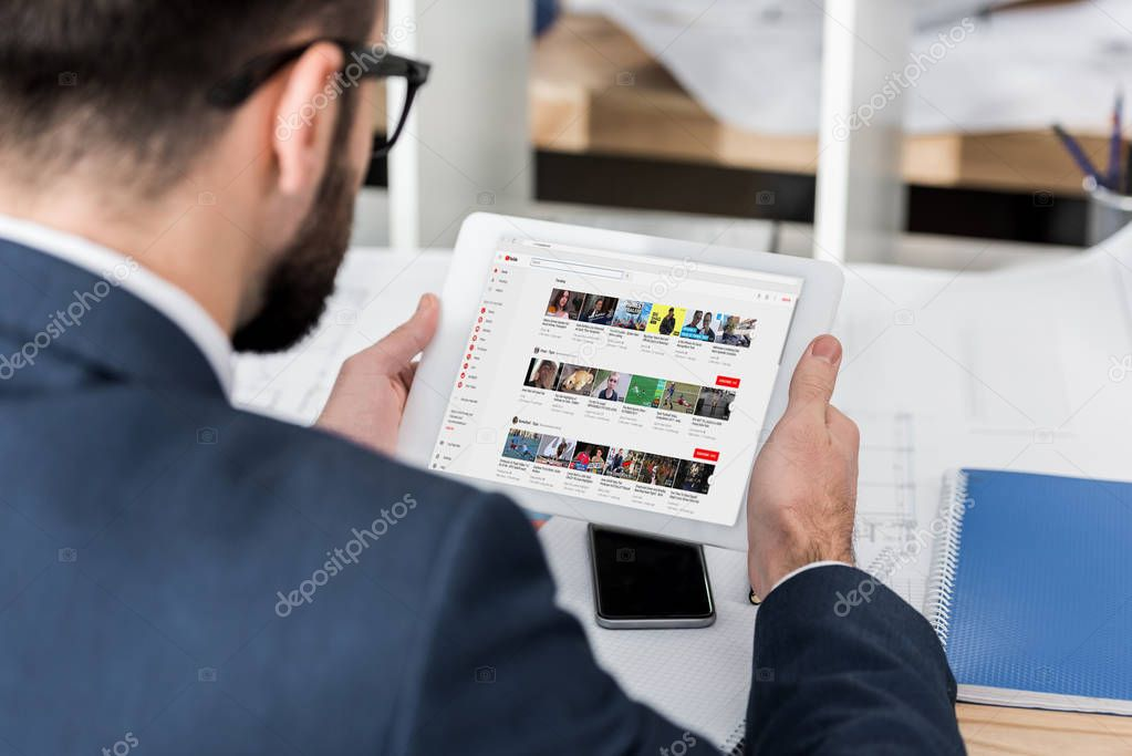 businessman holding tablet with loaded youtube page
