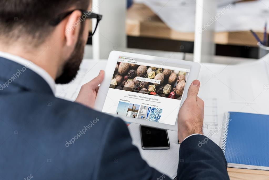businessman holding tablet with loaded depositphotos page