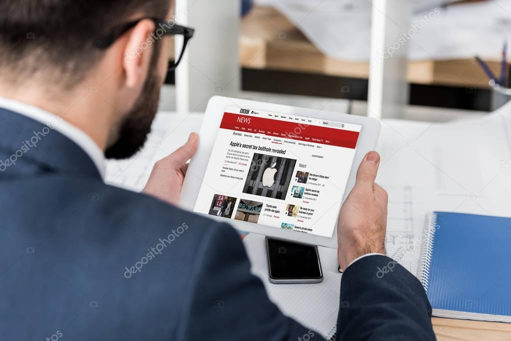 businessman holding tablet with loaded bbc news page