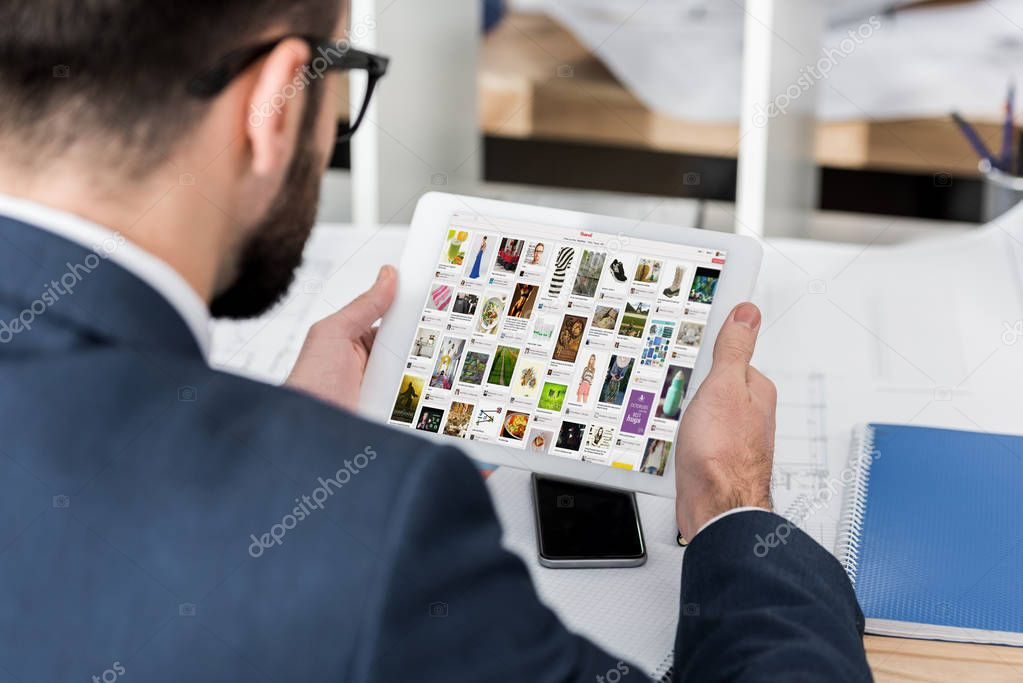 businessman holding tablet with loaded pinterest page
