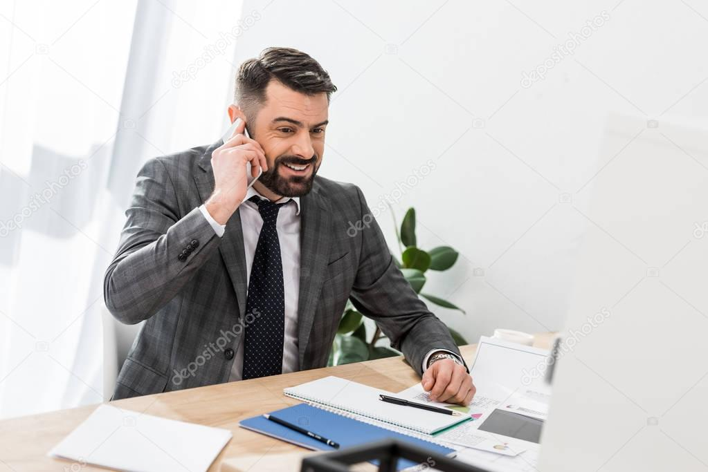 smiling businessman talking by smartphone at table in office