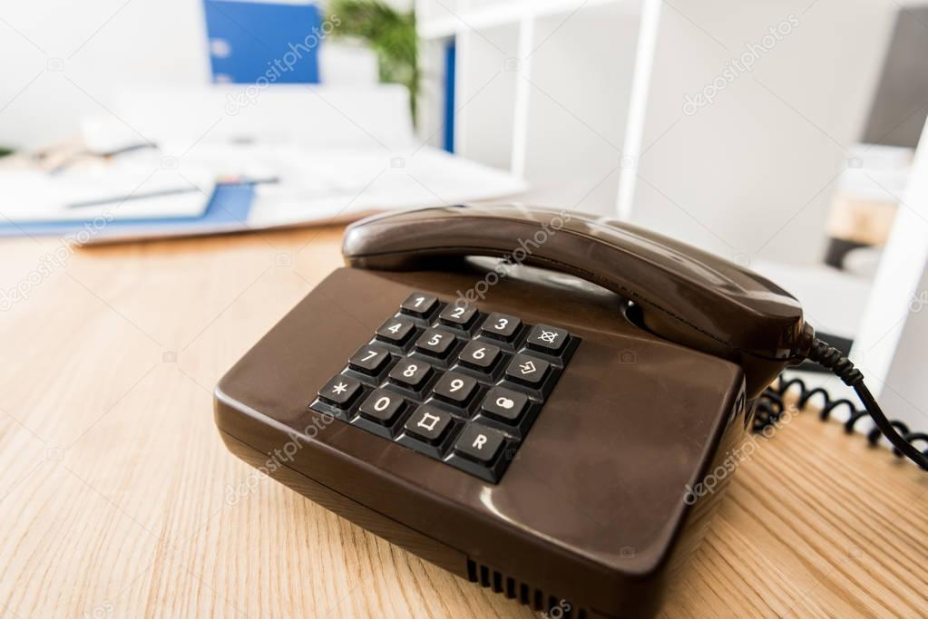 black stationary telephone on wooden table