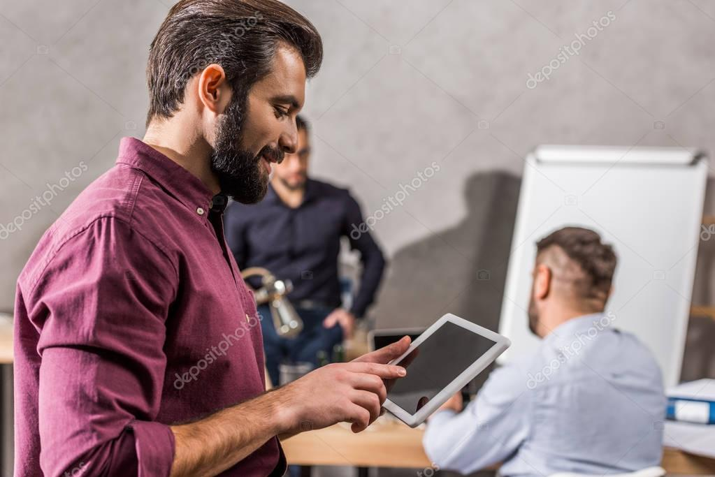 smiling businessman looking at tablet in office